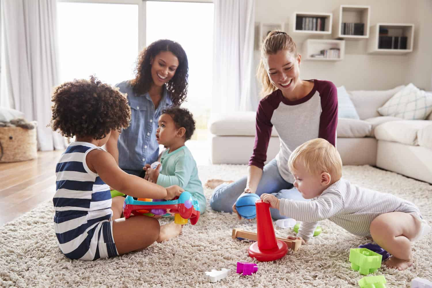 Photo of two friends playing with toddler kids on sitting room floor